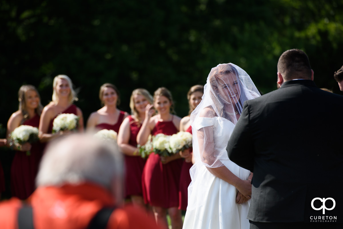Bride smiling at her groom during the outdoor wedding ceremony in Asheville ,NC.