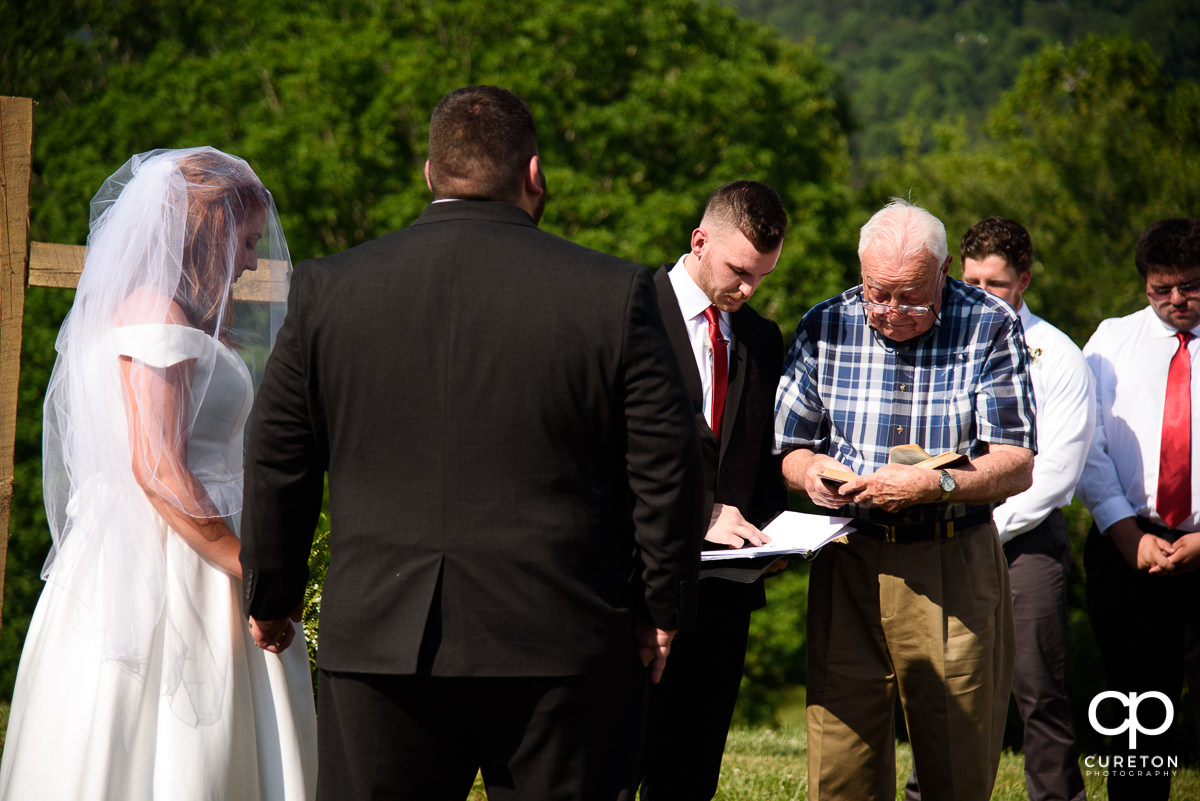 Grandfather praying during the outdoor wedding ceremony in Asheville,NC.