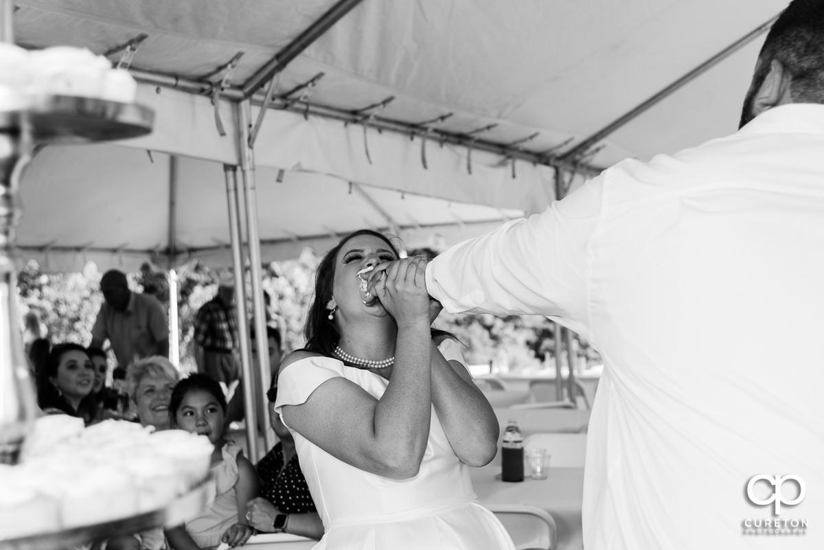Bride getting cake smashed in her face.