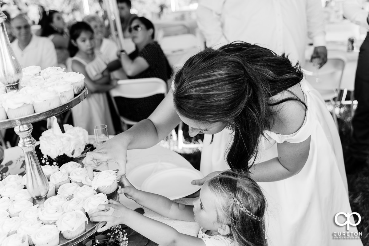 Bride helping the flower girl get a cupcake.