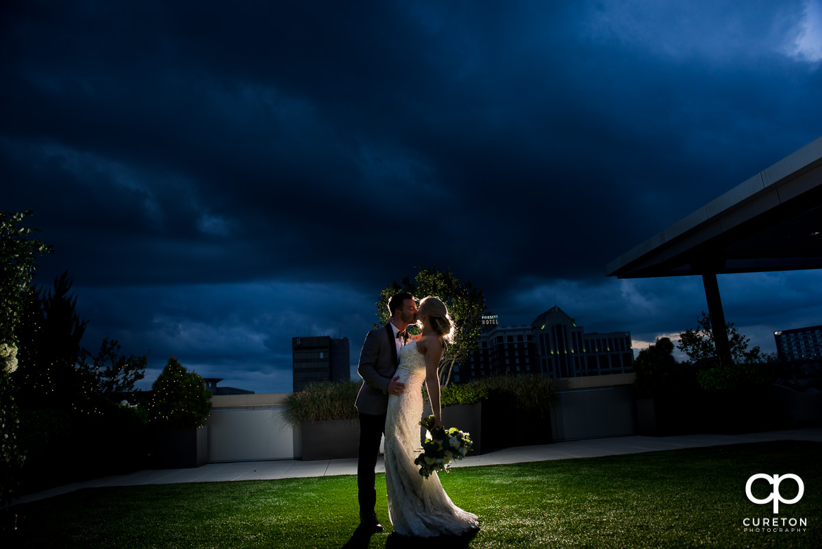 Groom kissing his bride under a deep blue sky after their rooftop wedding ceremony at Avenue in Greenville,SC.