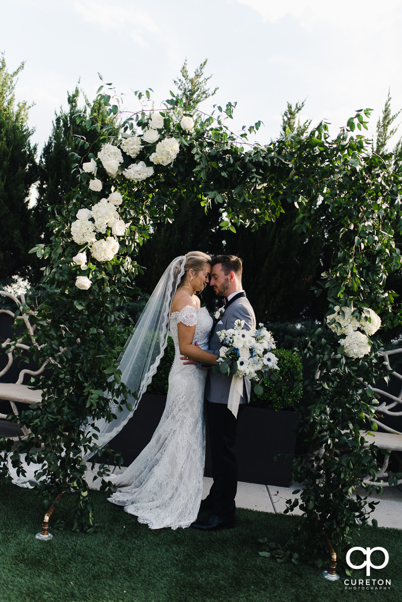 Bride and groom hugging underneath a flowered arch after their rooftop wedding ceremony at Avenue in Greenville,SC.