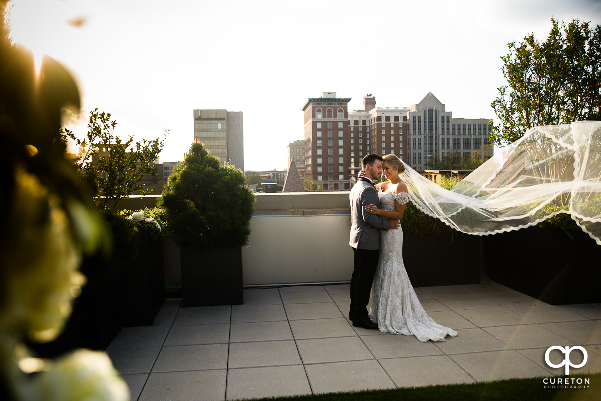 Bride and groom dancing as her veil blows in the wind after their wedding on the rooftop at Avenue in downtown Greenville,SC.