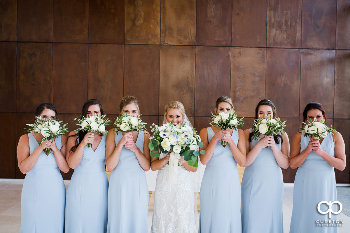 Bride and bridesmaids holding their flowers over their faces in Avenue.