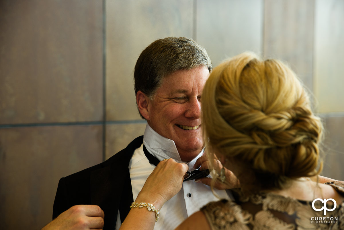 Bride's father putting on his tie.