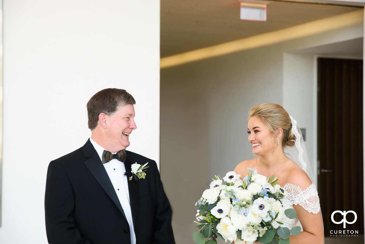 Bride smiling during first look with her father at Avenue in Greenville,SC.