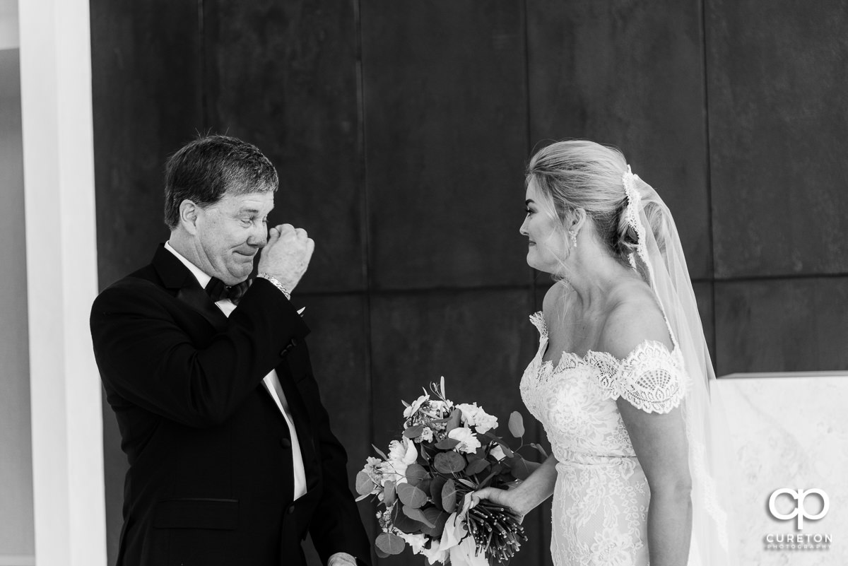 Bride's father wiping away tears after seeing his daughter on her wedding day.
