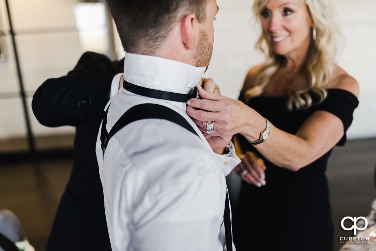 Groom's parents helping him get ready on his wedding day.