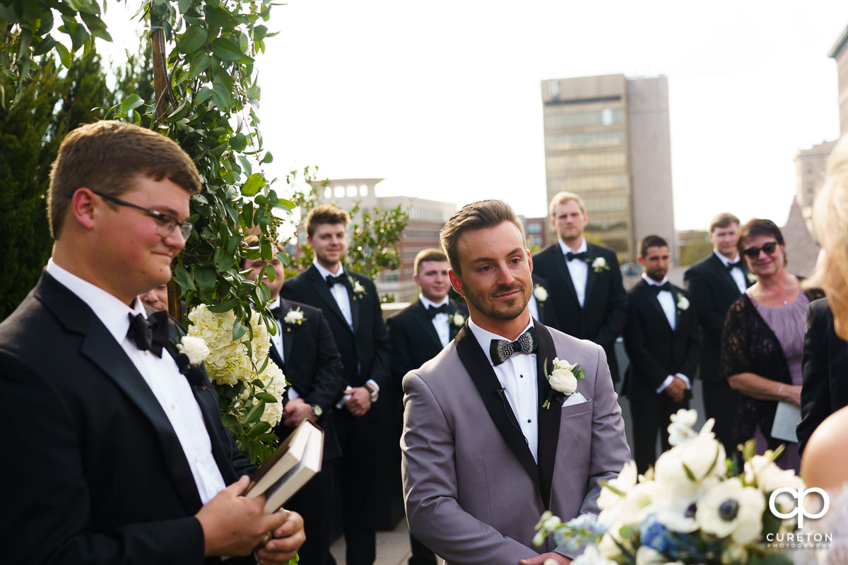 Groom as he sees his bride walking down the aisle at their rooftop wedding.