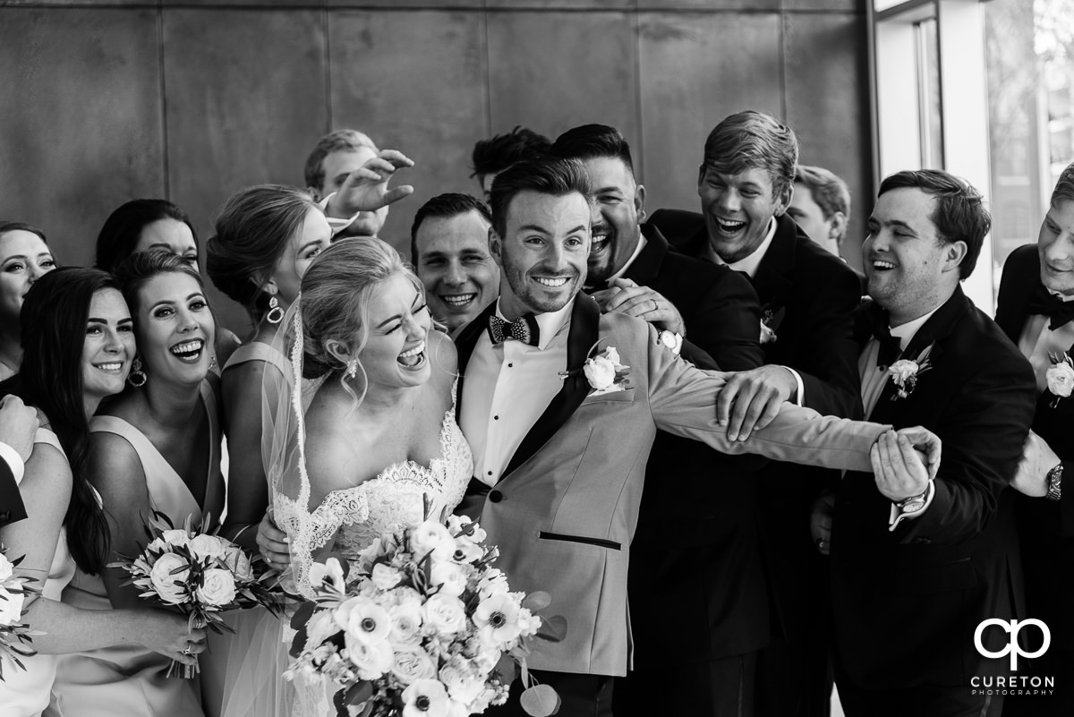 Bride and groom being hugged by the bridesmaids and groomsmen.
