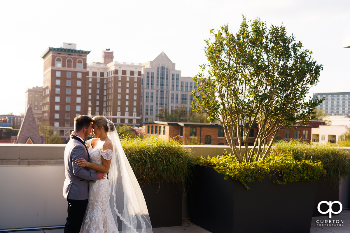 Bride and groom dancing in the sunlight on a rooftop.