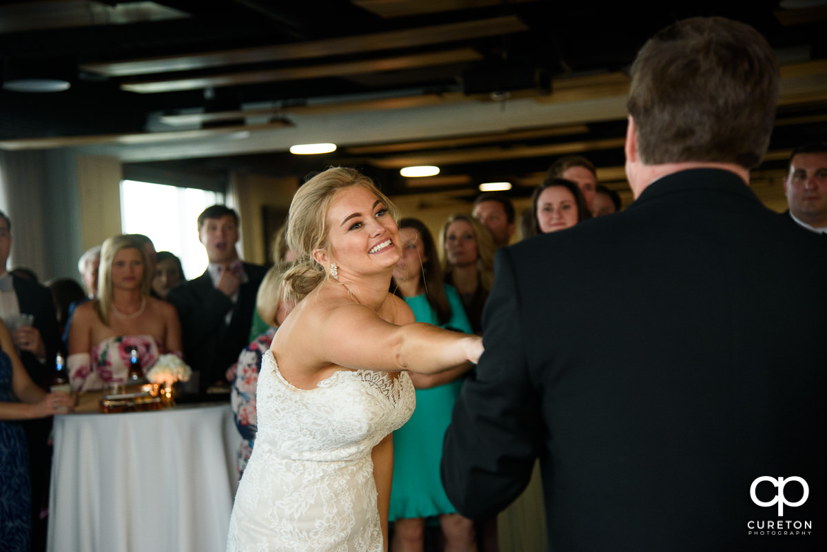 Bride smiling at her dad during the father-daughter dance.