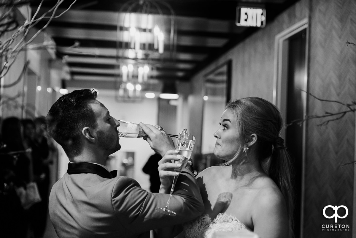Bride and groom drinking champagne.