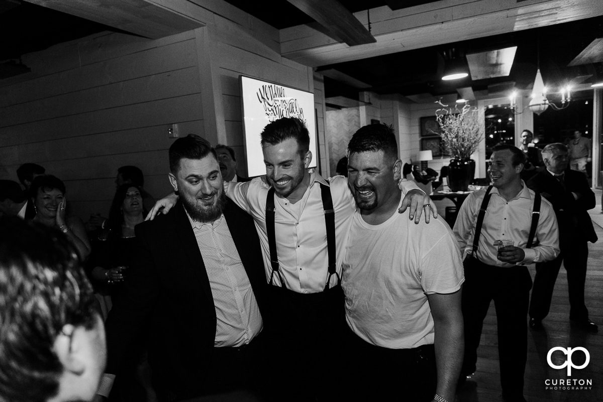 Groom laughing with friends at the reception.