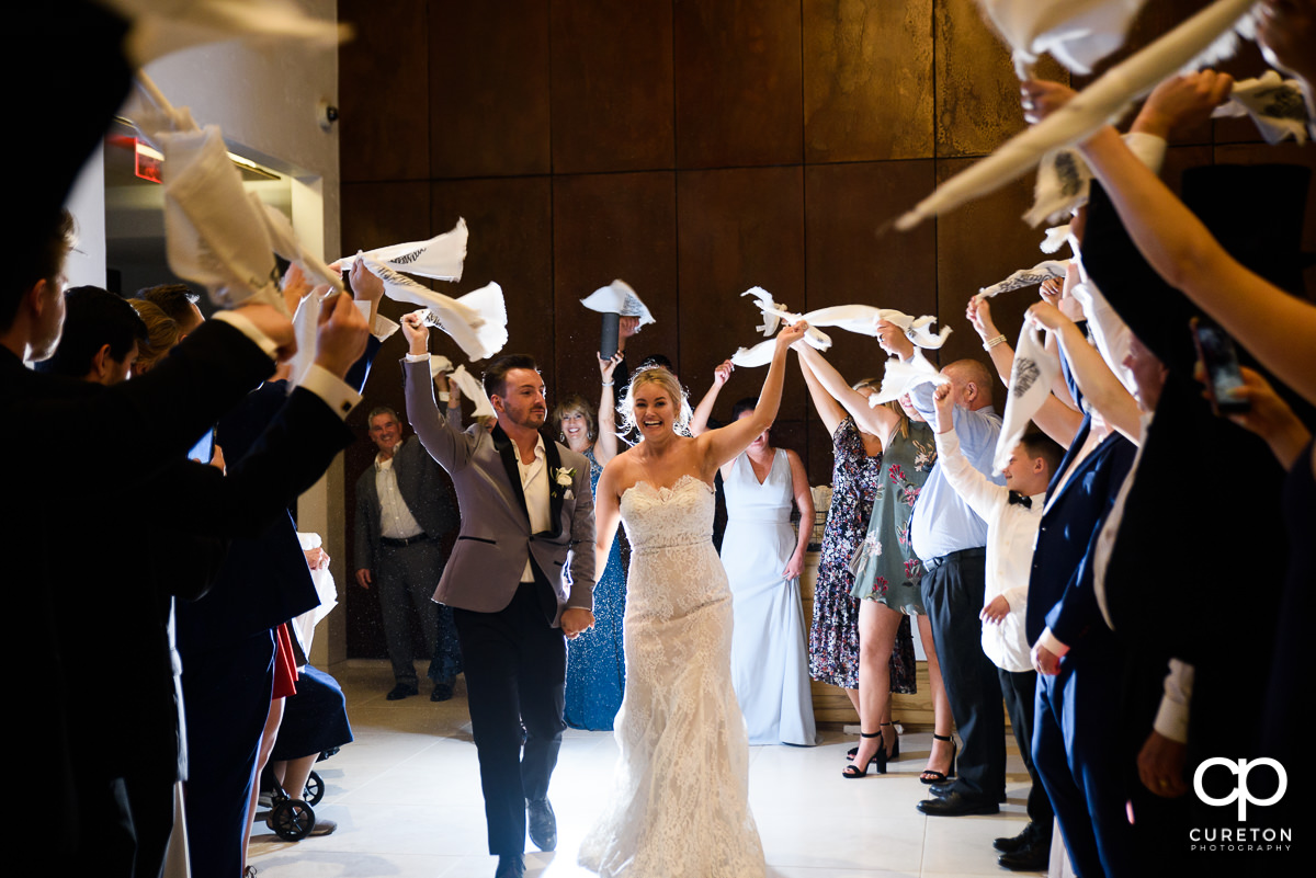 Bride and groom making an epic grand Gamecock exit at their wedding waiving towels as Sandstorm is played.