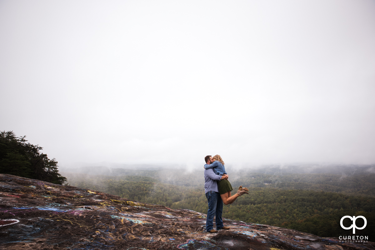 Man lifting his future bride as the fog lifts from the mountaintop during an engagement session at Bald Rock.