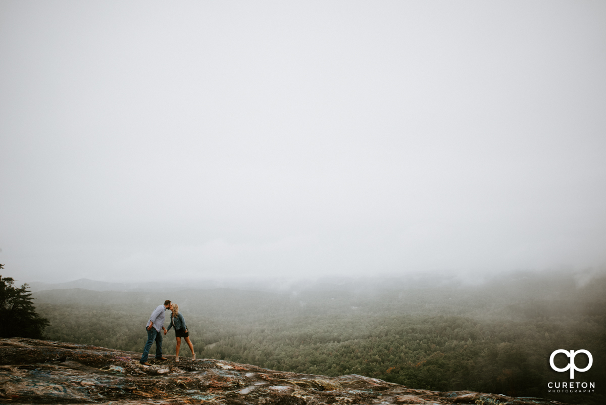 Engage couple kissing on top of a mountain during an engagement session at Bald Rock.