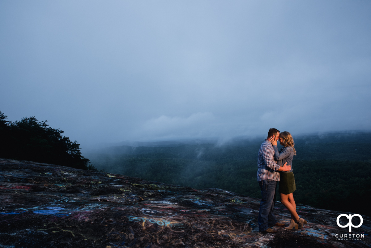 Engaged couple hugging on top of Bald Rock.