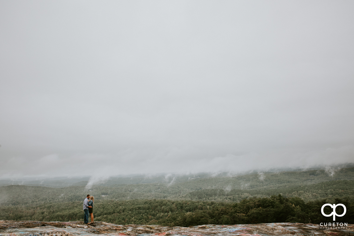 Couple on teh ledge of a mountain during an engagement session at Bald Rock.