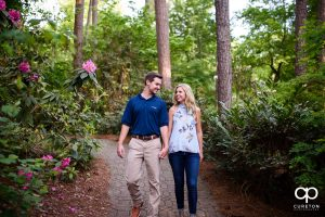 Couple holding hands walking down a trail at the Botanical Gardens in Clemson.