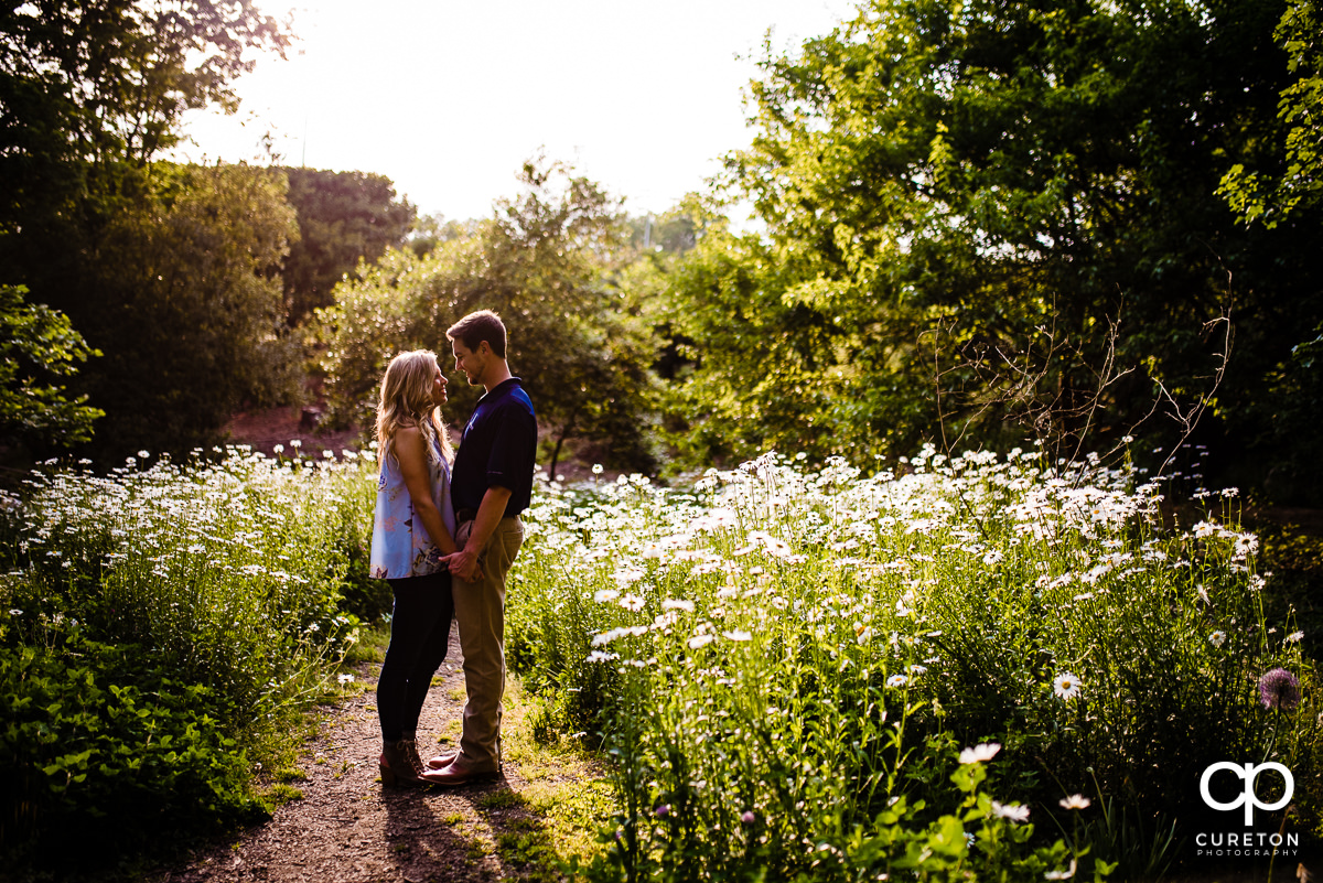 Engaged couple standing in white flowers at their engagement session in Clemson.