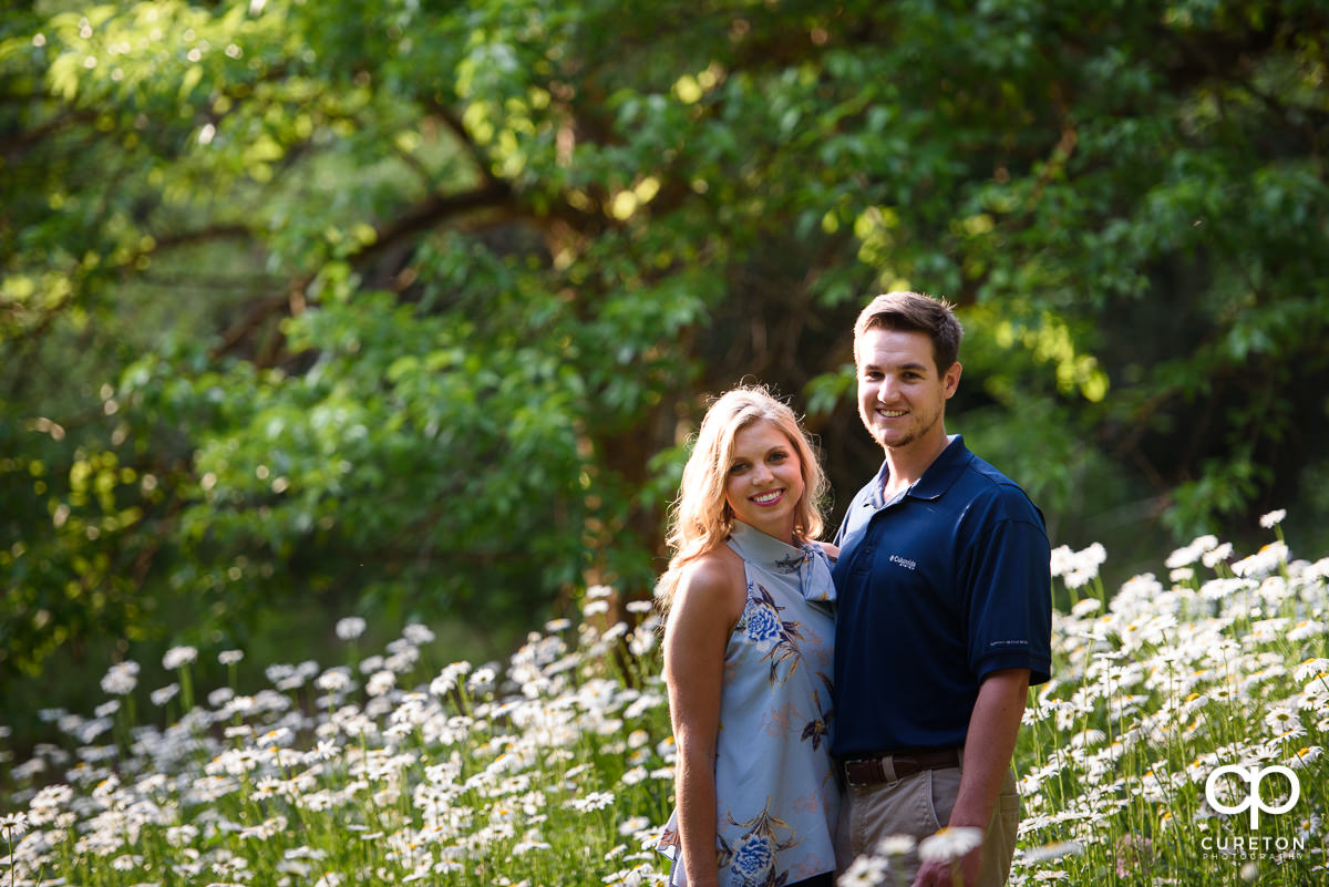 Engaged couple in a field of flowers.