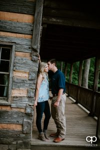 Man kissing his fiancee on the cheek at the Hunt Cabin at the Botanical Gardens in Clemson.