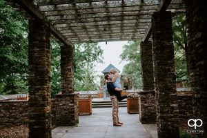 Man holding his fiancee in the air during their engagement session.