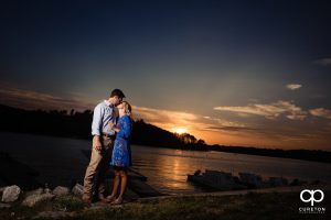 Future bride kissing her groom at sunset by the lake in Clemson.