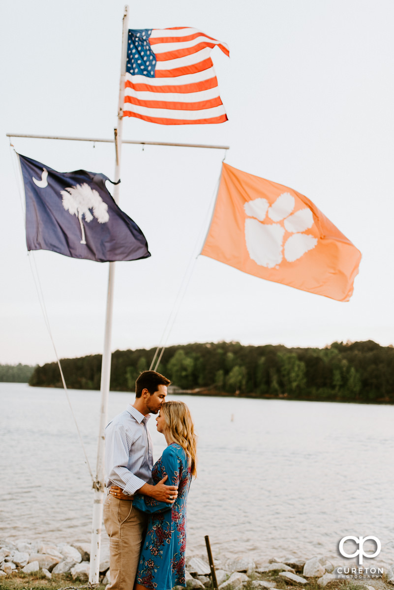 Man kissing his fiancee on the forehead underneath an American flag by the lake.