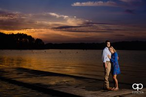 Engaged couple standing on a dock by the lake on the Clemson University campus.