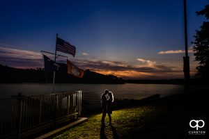 Epic engagement shot of a couple by the lake in Clemson at sunset.