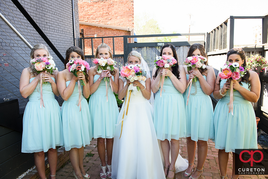 Brie and bridesmaids holding flowers over their faces..
