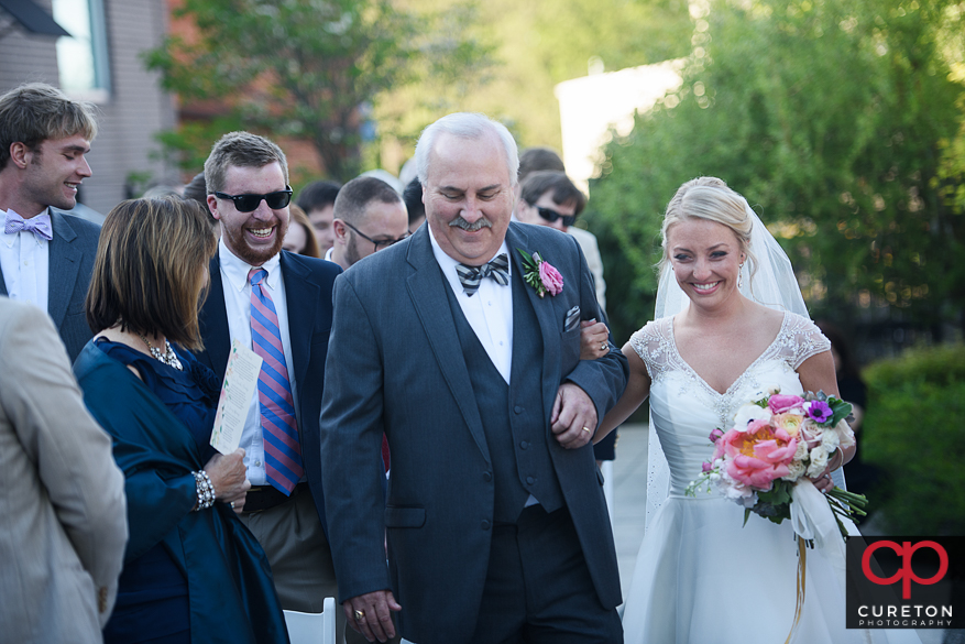 Bride and her father walking down the aisle at her outdoor wedding at Zen Greenville.
