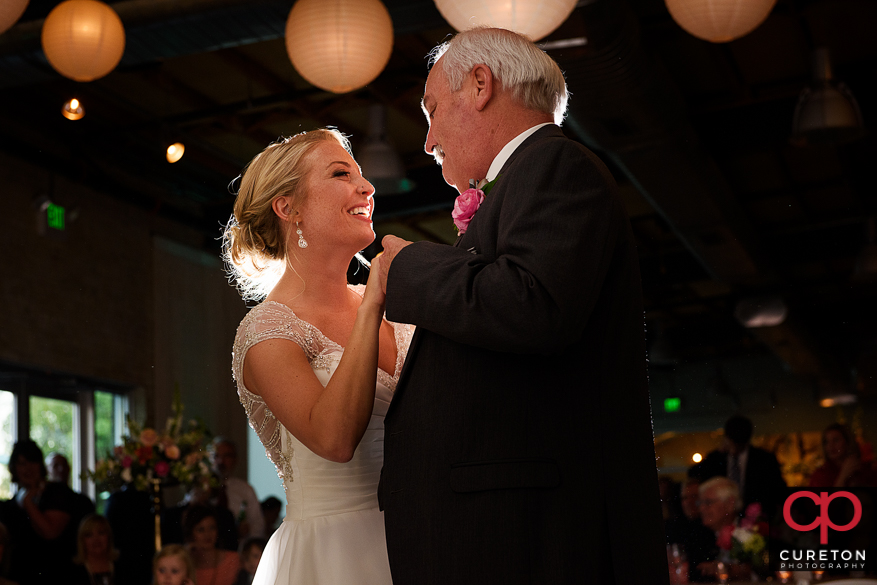 Bride and father are dancing.