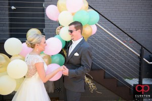 Bride and groom both holding balloons.