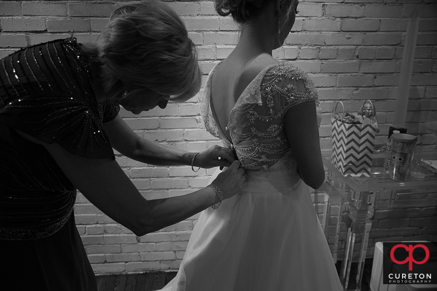 Bride's mom helps her in the dress.