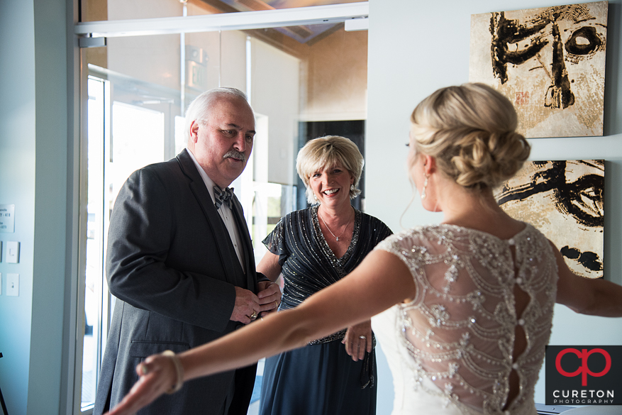 Bride's parent's see her for the first time in the dress.