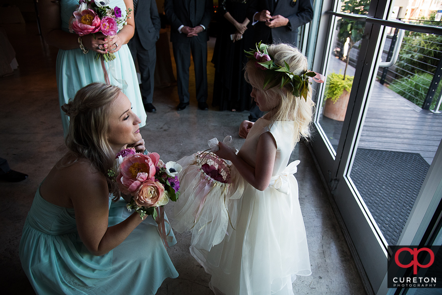 Bridesmaid talking to the flower girl.