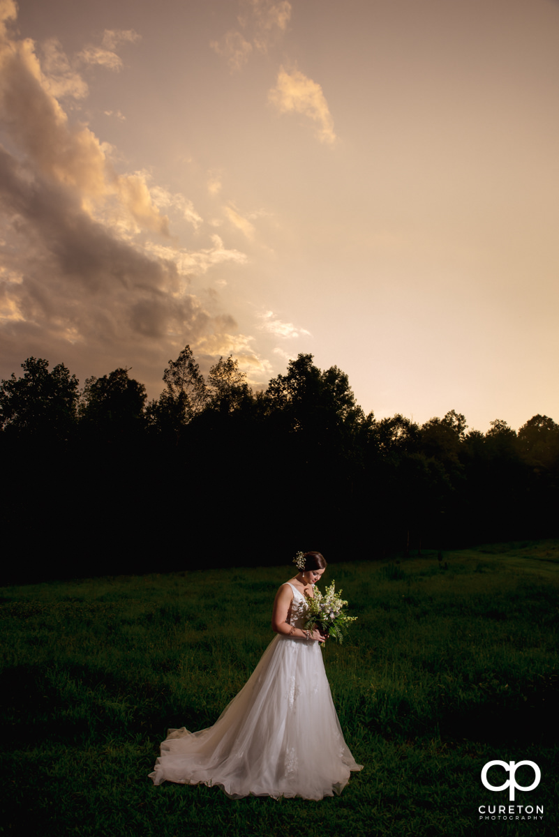 Bride looking at her flowers at sunset at a bridal session at Campbell's Covered Bridge in Greer,SC.