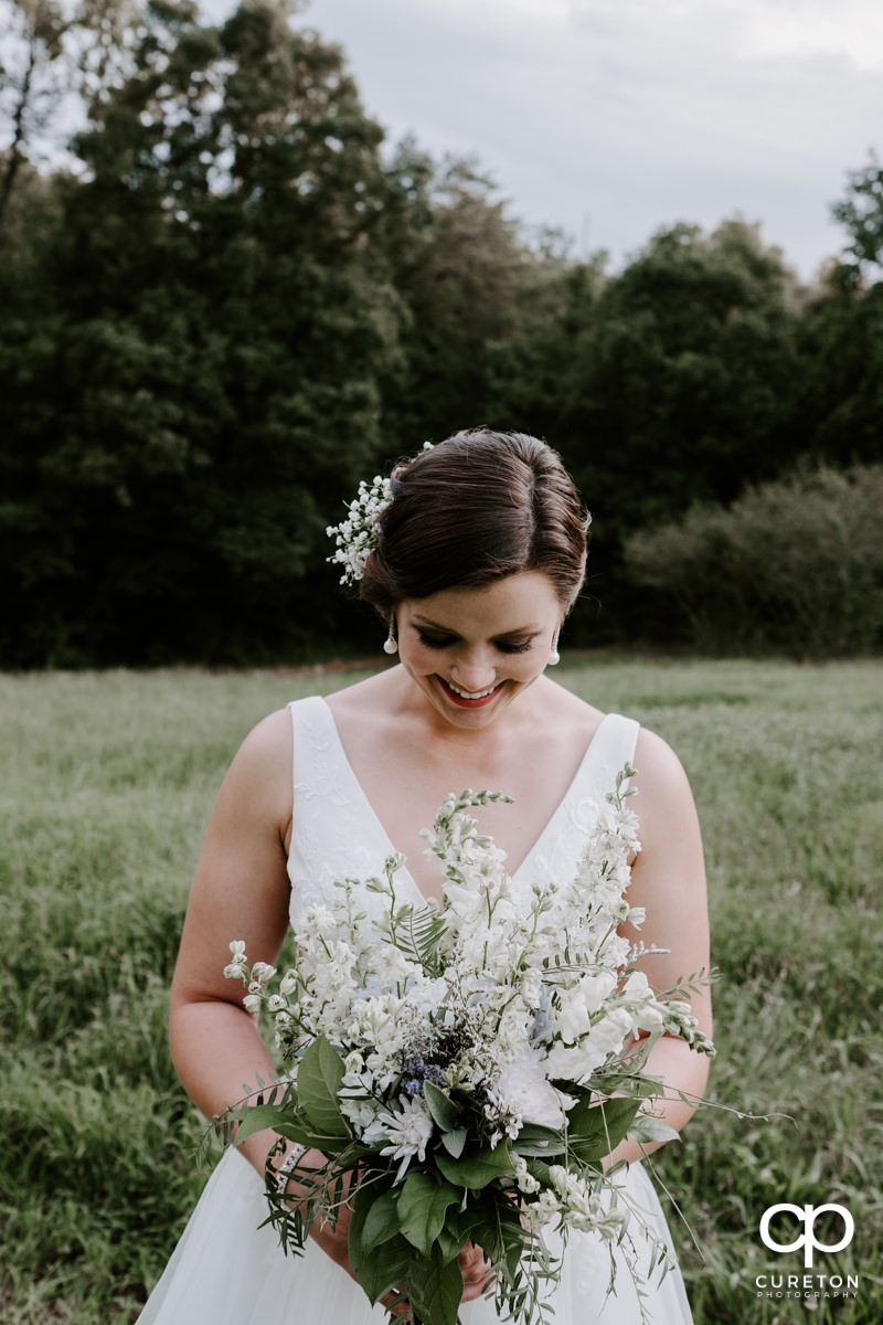 Bride smiling in a field holding her flowers at her bridal session.