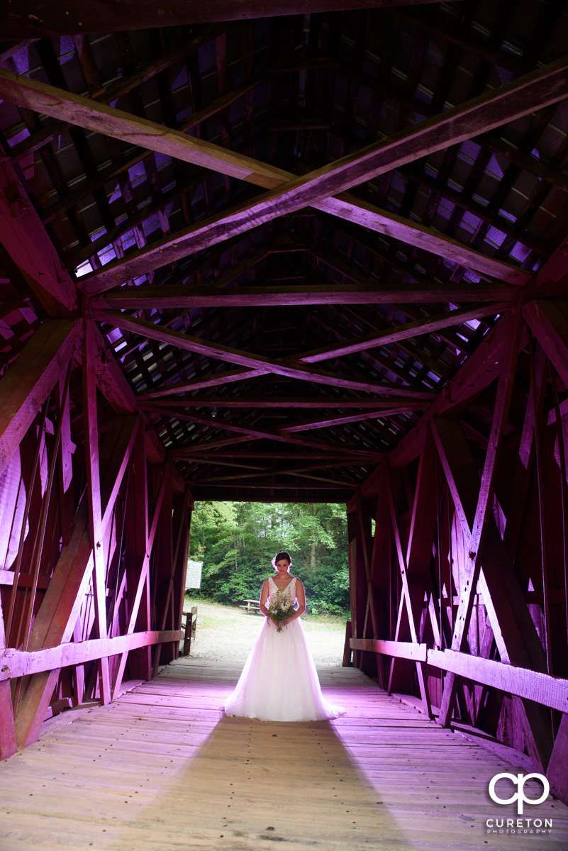 Bride holding her bouquet in a covered bridge as it is lit with purple lights.