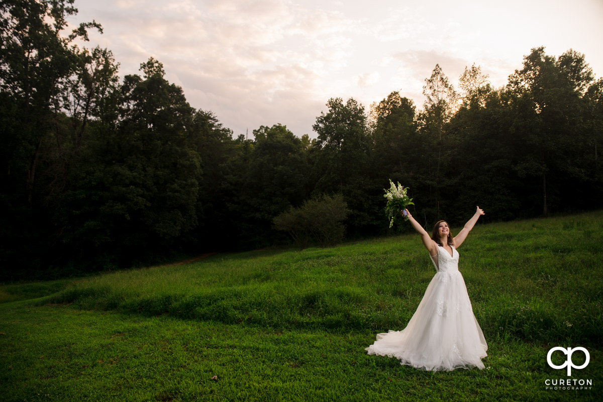Bride holding her hands in the air at her bridal session.