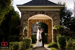 Bride and groom standing in an archway.
