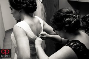Bridesmaid helping bride with her dress.