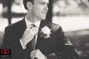 Groom straightening his tie.