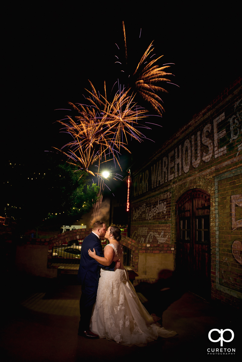 Bride and groom kissing as fireworks explode in the sky overhead at their wedding at the Old Cigar Warehouse in Greenville,SC.