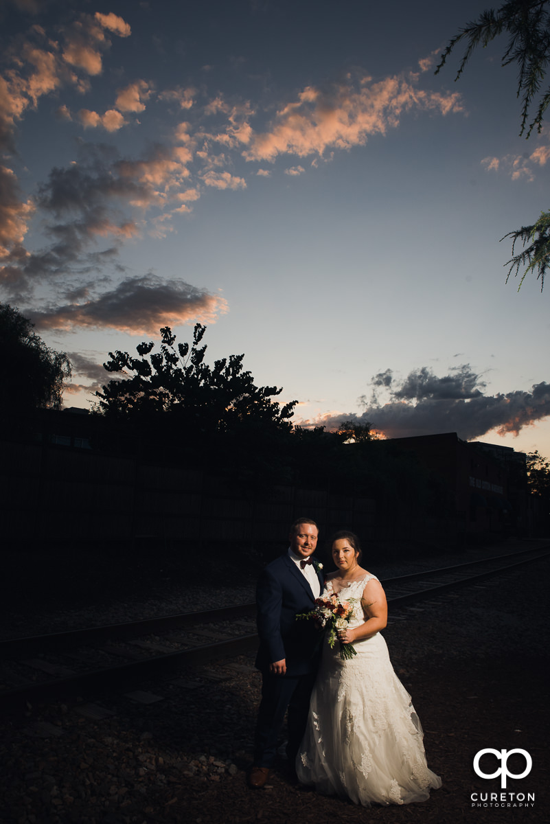 Bride and groom at sunset by the railroad tracks out back of Old Cigar Warehouse.