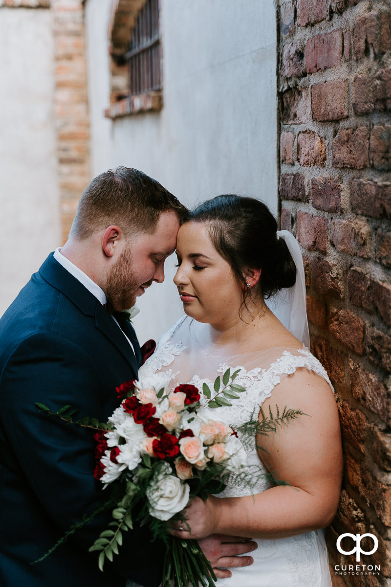 Groom and bride against a brick wall at The Old Cigar Warehouse.