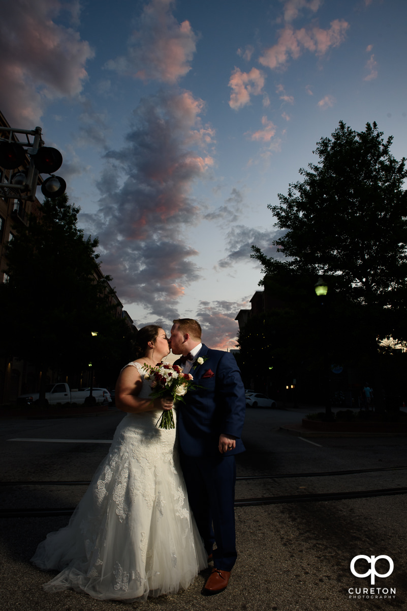 Bride and groom kissing in Main Street after their wedding at the Old Cigar Warehouse in downtown Greenville,SC.